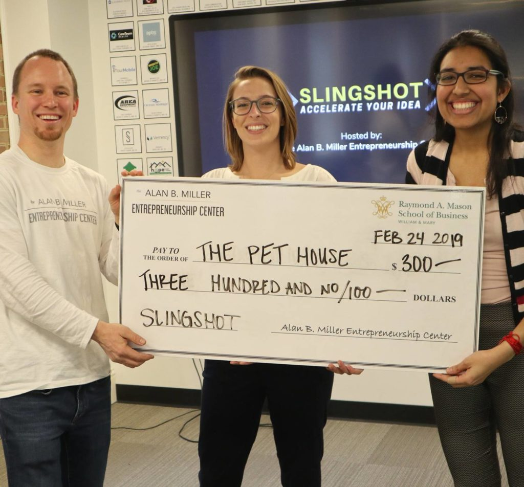 Photo of two Students and a professor holding a large check at the Entrepreneurship Center.