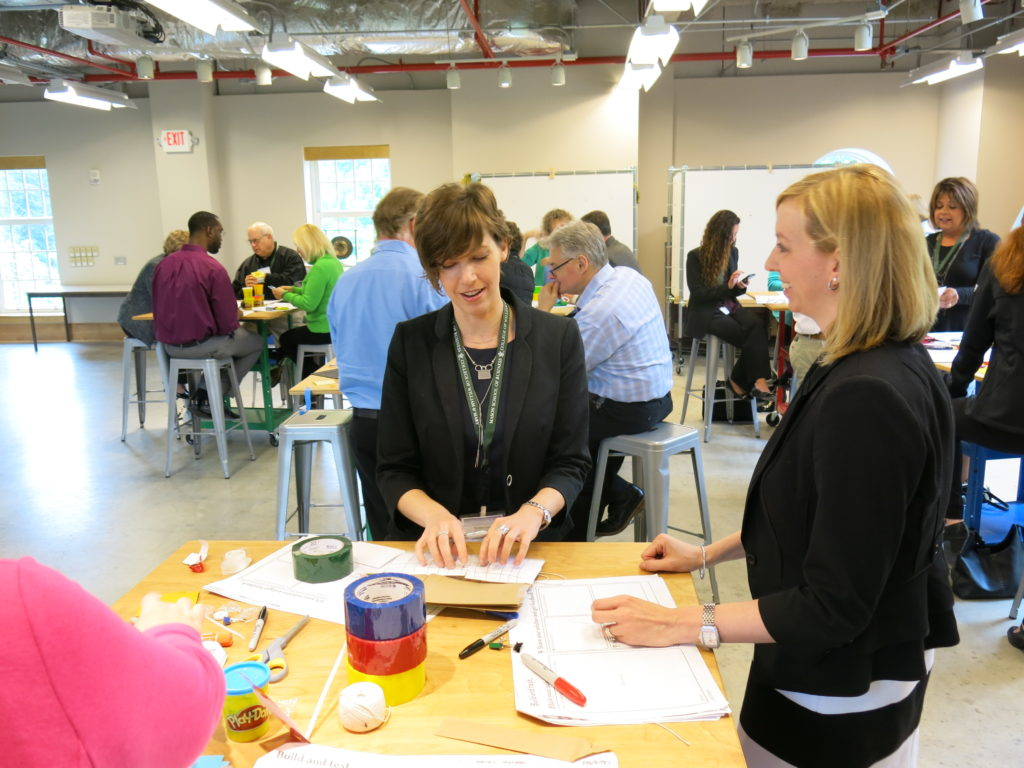 Photo of Business People creating prototypes at worktables.